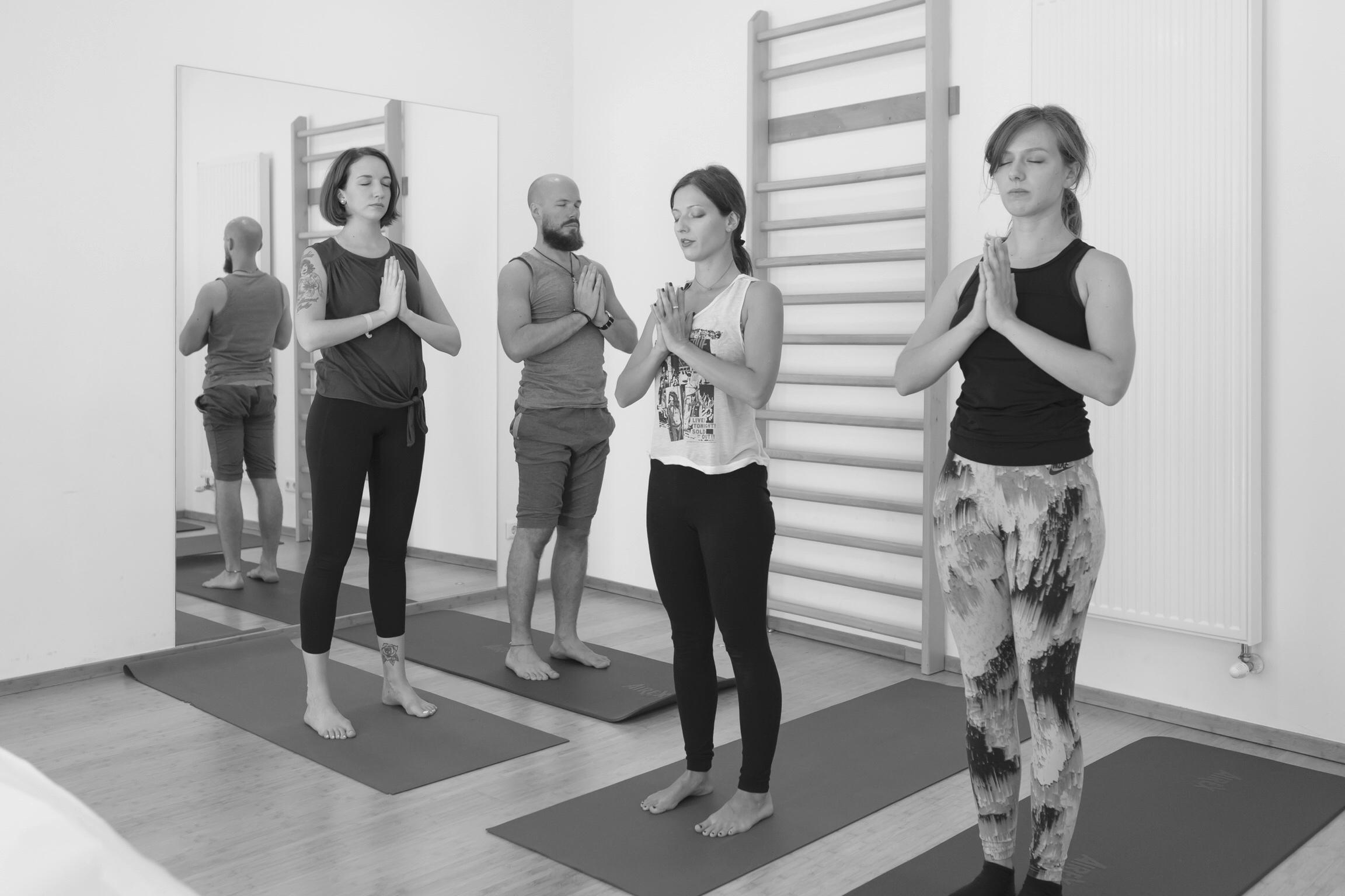 Yoga Gruppe im Stehen mit Händen in Gebetshaltung