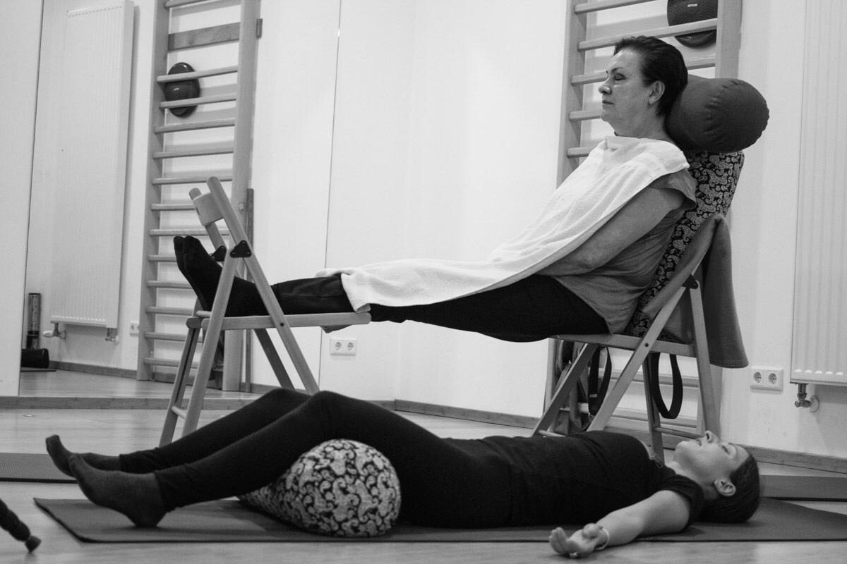 Zwei Personen liegen und machen Yoga