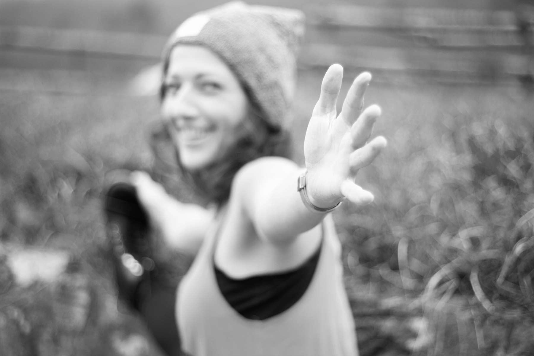 Person macht eine Yogaübung und streckt die Hand in Richtung Kamera