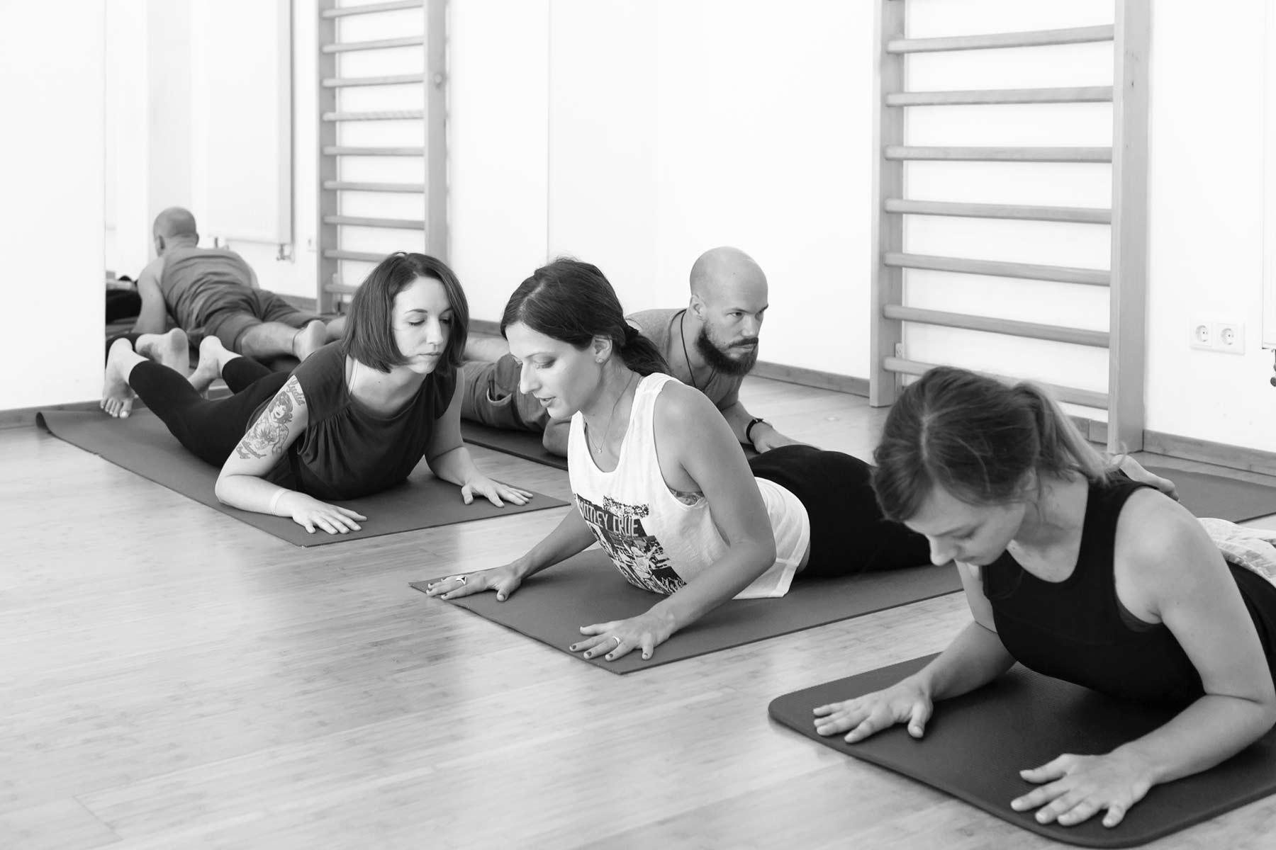 Personen liegen auf Yogamatten und machen sanfte Yogaübungen